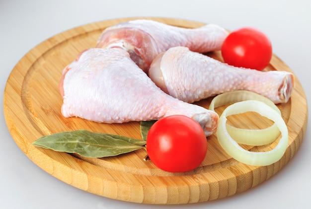 Cuisses de poulet crues sur fond blanc