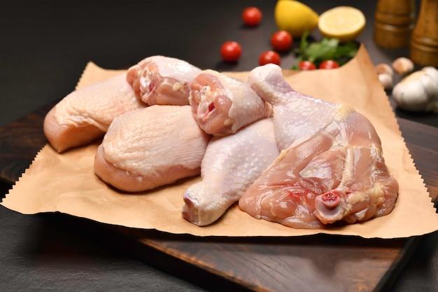 Cuisses de poulet crues fraîches et cuisses de poulet pour la cuisson sur un papier d'emballage avec des ingrédients sur une planche à découper