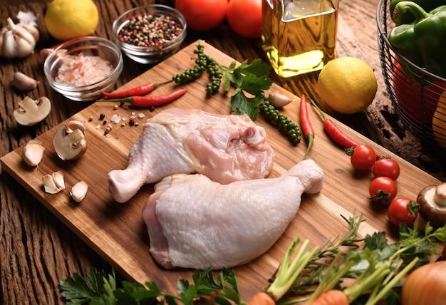 Cuisses de poulet crues fraîches avec des ingrédients pour la cuisson sur une planche à découper en bois