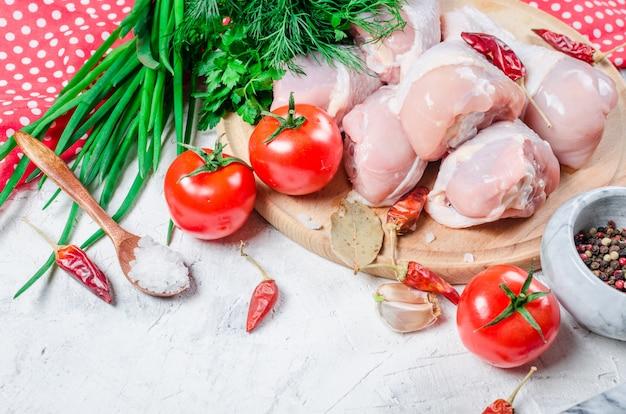 Cuisses de poulet crues sur une planche à découper avec des épices et des herbes.