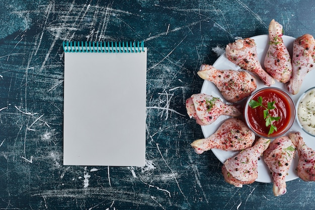 Cuisses de poulet crues sur un plateau blanc avec un livre de recettes de côté.