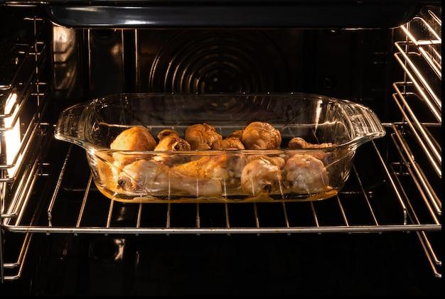 Les cuisses de poulet dans un plateau en verre sont cuites au four