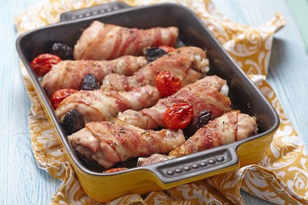 Cuisses de poulet enrobées de bacon avec tomates et olives