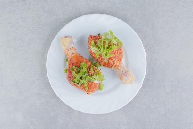 Cuisses de poulet épicées crues dans l'assiette, sur la surface blanche