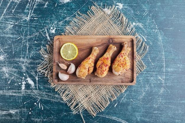 Cuisses de poulet épicées frites sur une planche de bois.