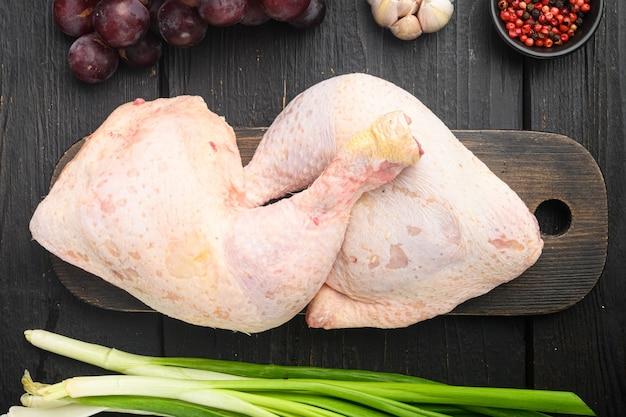 Cuisses de poulet frais et ensemble d'ingrédients de marinade, sur une planche à découper en bois, sur une table en bois noir, vue de dessus à plat