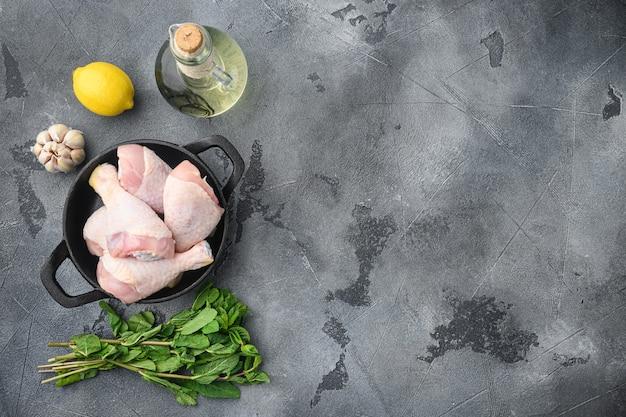 Cuisses de poulet frais et ensemble d'ingrédients de marinade, sur une poêle en fonte, sur table grise, vue de dessus à plat