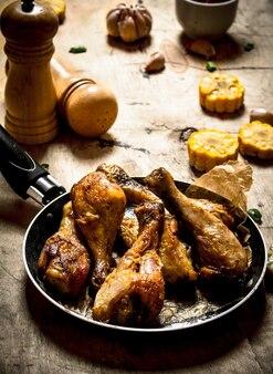 Cuisses de poulet frites avec du maïs et de l'ail. sur une table en bois.