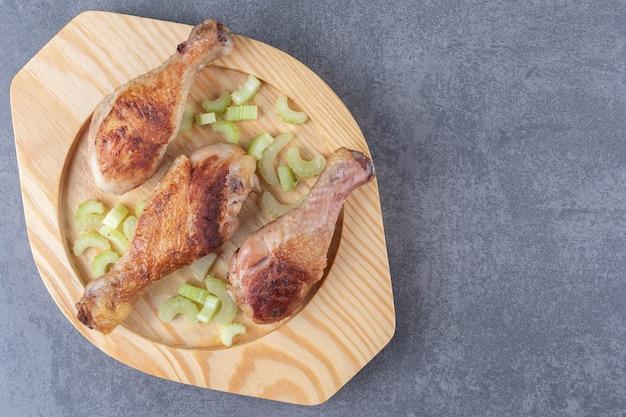 Cuisses de poulet frites sur plaque de bois.