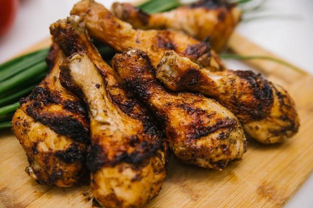 Les cuisses de poulet frites reposent sur une planche de bois. poulet shish kebab avec un accompagnement de légumes.