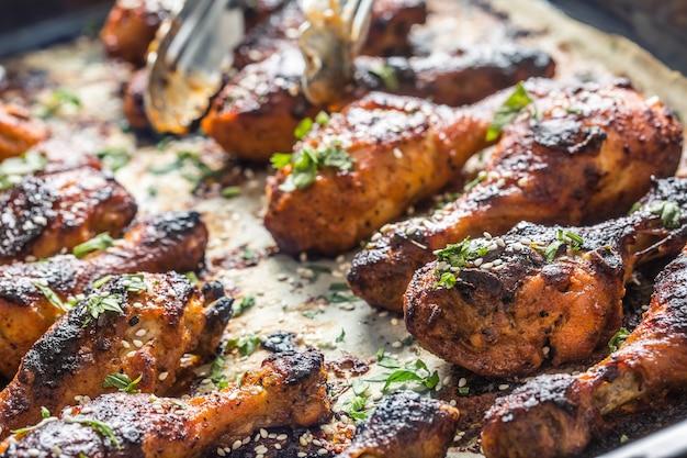 Cuisses de poulet grillées bbq aux épices, herbes et sésame sur papier cuit. farine de volaille rôtie dans un plat à rôtir.