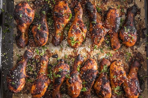 Cuisses de poulet grillées bbq aux épices, herbes et sésame sur papier cuit - haut de la vue. farine de volaille rôtie dans un plat à rôtir.