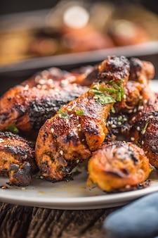 Cuisses de poulet grillées bbq aux épices, herbes et sésame sur papier cuit. repas de volaille rôtie sur plaque blanche.