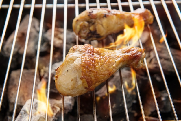 Cuisses de poulet grillées sur des flammes sur un barbecue.