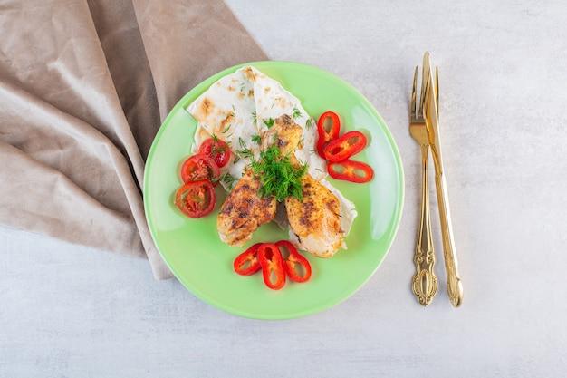 Cuisses de poulet grillées maison avec du pain plat sur plaque verte.
