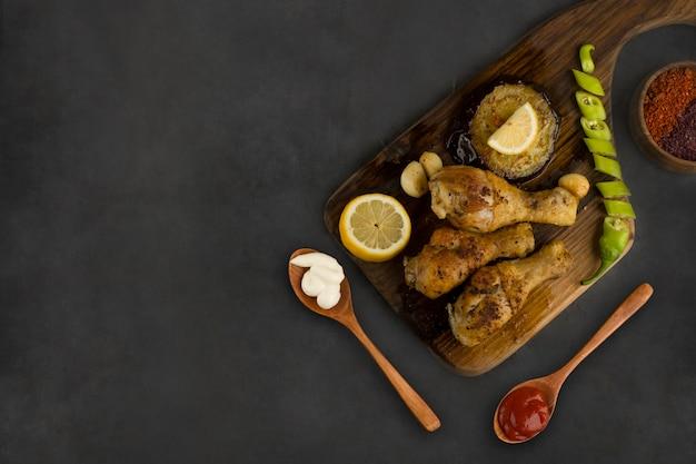 Cuisses de poulet grillées servies avec citron, chili et sauces