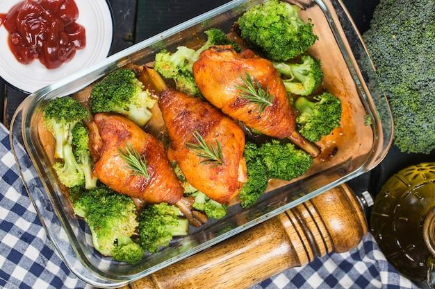 Cuisses de poulet avec des légumes sur une table en bois.