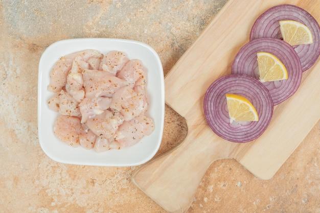 Cuisses de poulet non cuites dans une assiette blanche avec des tranches d'oignon