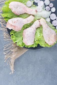 Cuisses de poulet non cuites et oignon émincé sur tableau noir.