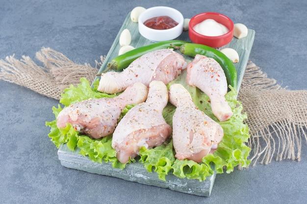 Cuisses de poulet non cuites et piments sur planche de bois.