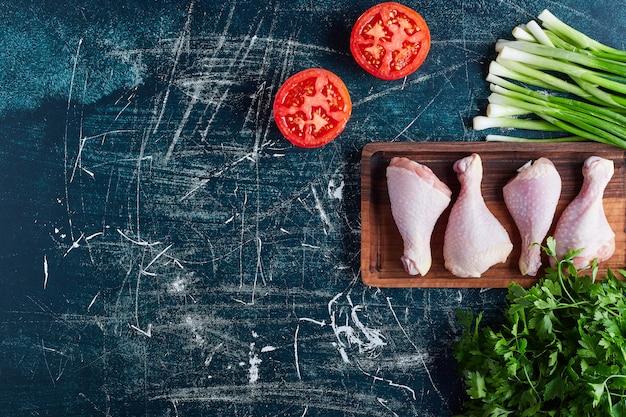 Cuisses de poulet sur une planche de bois.