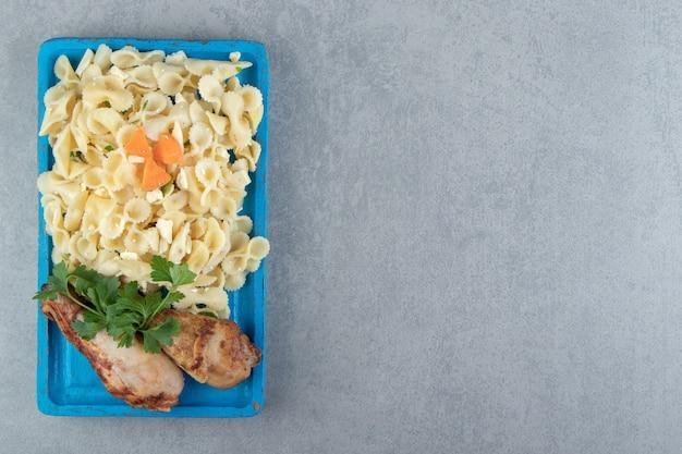 Cuisses de poulet poulet avec de savoureuses pâtes sur plaque bleue.