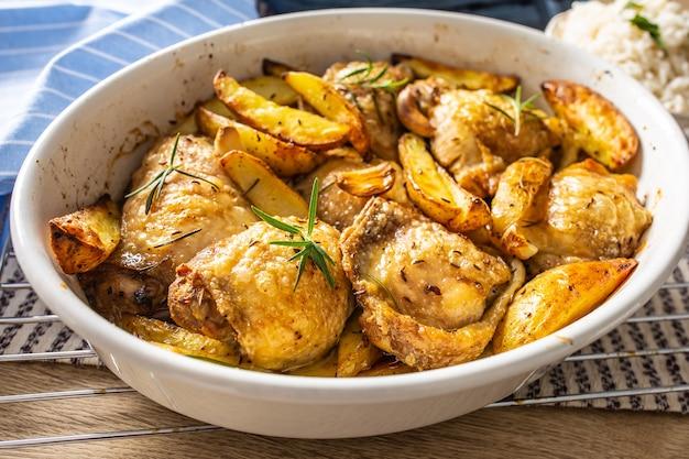 Cuisses de poulet rôties avec pommes de terre américaines dans un plat allant au four.