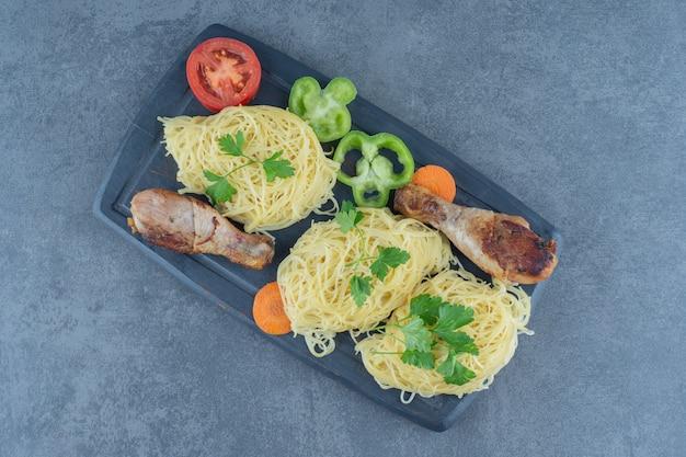 Cuisses de poulet et spaghettis sur planche de bois.