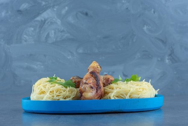 Cuisses de poulet et spaghettis sur plaque bleue. k