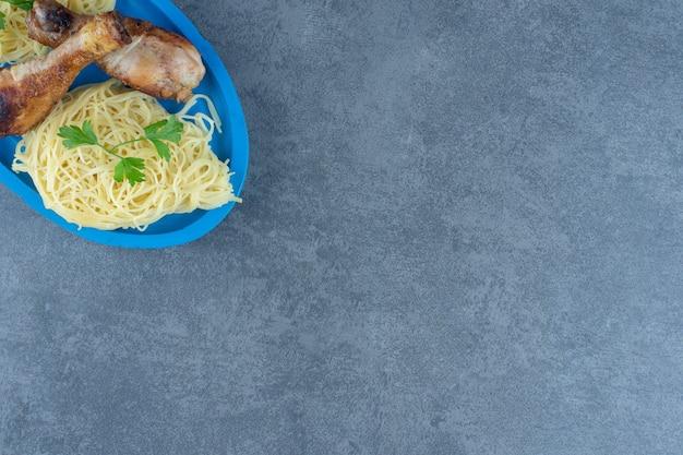 Cuisses de poulet et spaghettis sur plaque bleue.