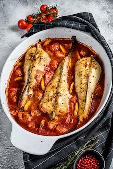 Cuisson aux tomates de la lotte dans un plat allant au four. fruits de mer frais