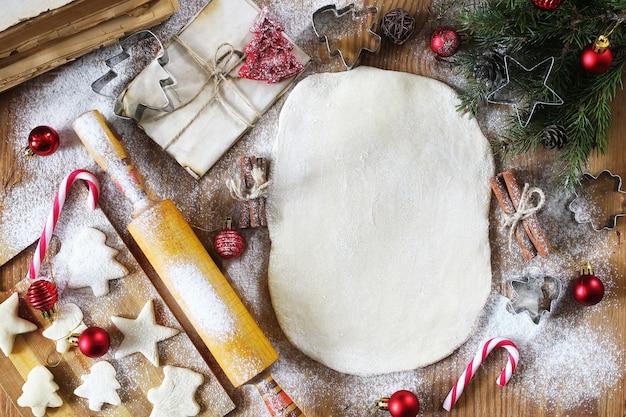 Cuisson des biscuits au beurre de différentes formes sur une table en bois avec des accessoires de noël
