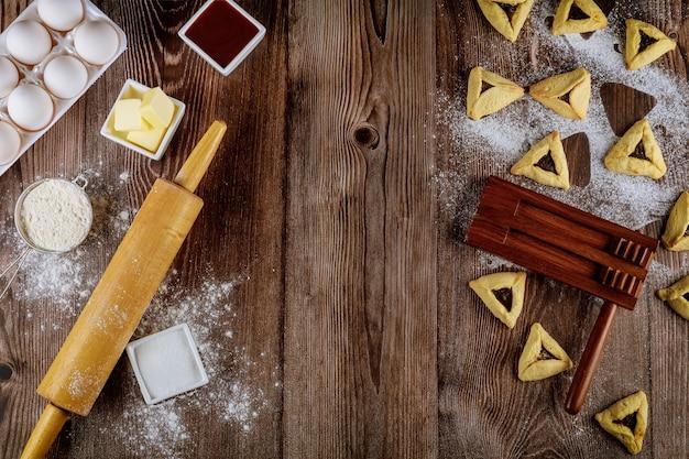Cuisson des biscuits juifs hamantaschen avec des ingrédients pour pourim.