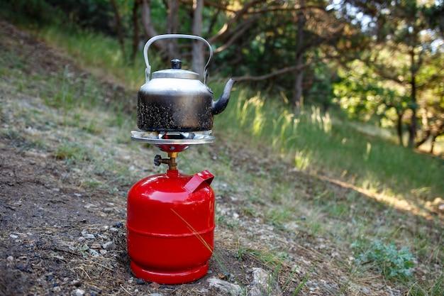 Cuisson de la bouilloire de camping sur une bouteille de gaz rouge.