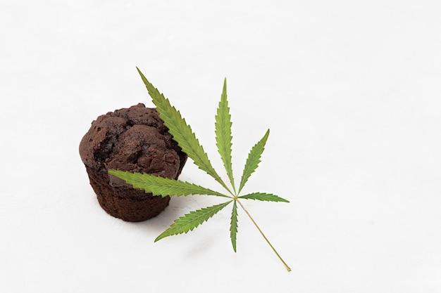 Cuisson avec le concept de cannabis brownie cupcake avec feuille de cannabis sur fond neutre avec espace de copie