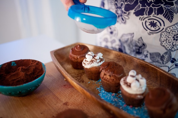 Cuisson des cupcakes, des muffins et une assiette d'ingrédients pour la décoration sur la table