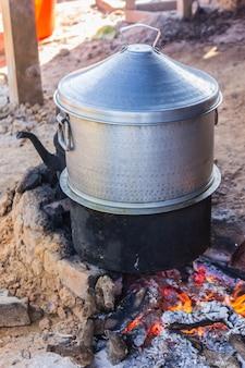 Cuisson du riz avec un pot sur un brasero à charbon