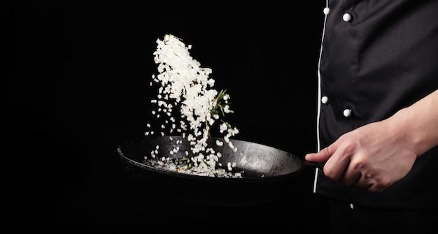 Cuisson du sel aromatique rôti dans une casserole à la main du chef.