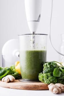 Cuisson du smoothie vert dans un mélangeur sur un fond clair.
