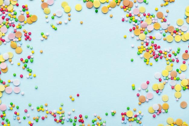 La cuisson du sucre arrose coloré en forme de cercle. cadre rond avec garniture de pâtisserie. espace de copie vide au centre. ingrédient de pâtisserie de gâteau sucré. isolé sur fond bleu. notion de vacances.
