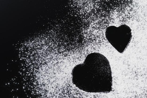 Cuisson de fond avec forme de coeur et farine sur une table sombre avec espace de copie