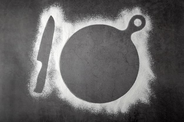 Cuisson fond sombre avec des contours de planche à découper de farine et de couteau à plat et place pour le texte