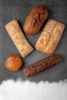 Cuisson fond sombre avec différentes pains de pain cuit au four vue de dessus sur une surface grise au centre et de la farine