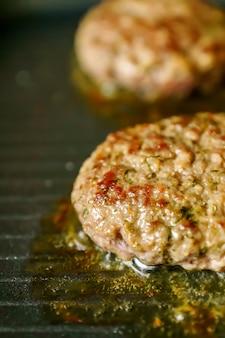 Cuisson des hamburgers à la viande avec des épices sur le gril à la maison. gros plan, mise au point sélective