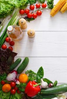 La cuisson des légumes frais sur bois blanc avec espace copie