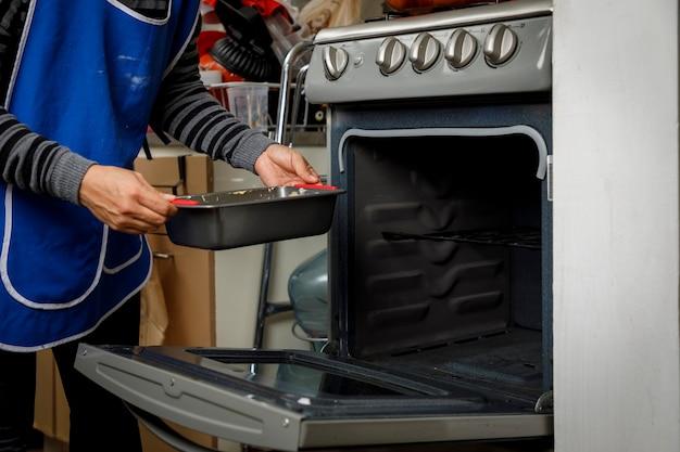 Cuisson à la maison femme vérifiant la cuisson d'une crêpe dans le four de la cuisinière