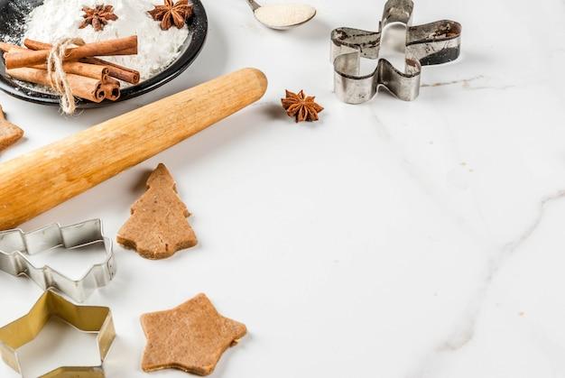 Cuisson de noël. pâte de gingembre pour pain d'épice, hommes de pain d'épice, étoiles, arbres de noël, rouleau à pâtisserie, épices (cannelle et anis), farine. sur la table en marbre blanc de la cuisine à domicile. espace copie