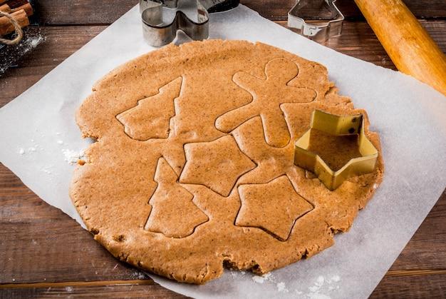 Cuisson de noël pâte de gingembre pour pain d'épice hommes de pain d'épice étoiles arbres de noël rouleau à pâtisserie épices (cannelle et anis) farine sur la table de marbre blanc de cuisine à domicile