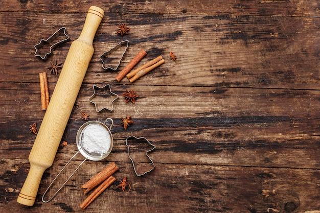 Cuisson de noël, ustensiles de cuisson, épices, emporte-pièces - étoiles, ange et sapin, tamis, sucre en poudre et un rouleau à pâtisserie. planches en bois anciennes