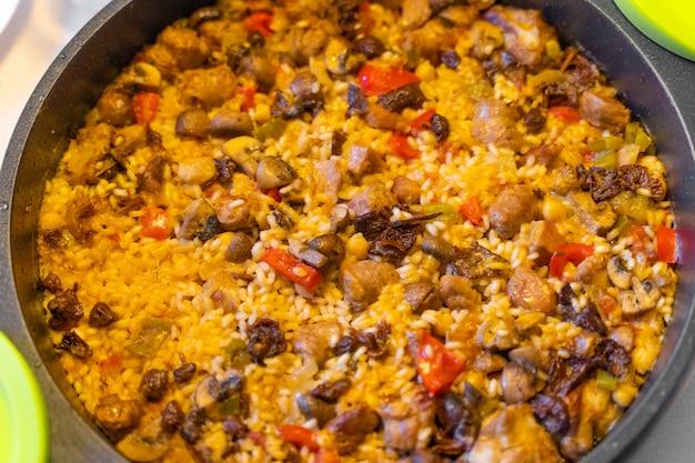 Cuisson de la paella de riz au poulet avec de la viande, des champignons et des légumes paella espagnole avec du bouillon de poulet